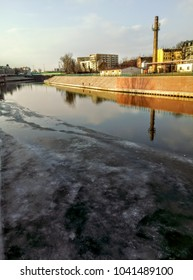 Thaw on the river in the city. Industrial enviroment, chimneys and fabrics. Buildings above icy water. Frost on steam surface. Urban scenery, architecture and nature. Early spring first signs.