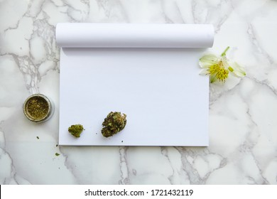 THC and CBD Cannabis Flower and Joint on Drawing Notepad on marble table. Blank space for text.