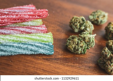 THC / CBD infused sour candy straws and marijuana buds on wood background