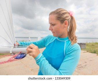 The girl prepares for a yacht for competitions
