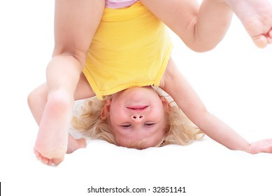 The little girl is turned upside down