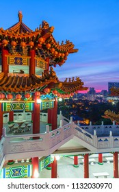 Thean Hou Buddhist Temple decorated with lanterns at dusk with the city skyline on the background, Kuala Lumpur, Malaysia