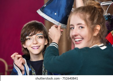 Theater assistant helps student dress for part as wizard in dressing room