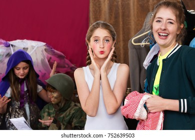 Theater assistant laughs as the young actress pouts at the camera