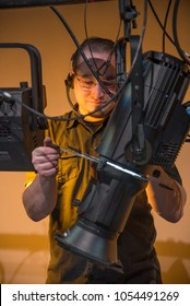 Theater lighting technician adjusting focus of lighting elements backstage next to a let cyclorama curtain.