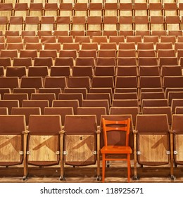 Theater seats, front side, one red seat, seventh place, first row, background