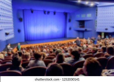 Theatre stage. Blue curtain. Defocused image, bokeh effect. People in the auditorium of the theater or concert hall.