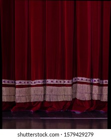 Theatrical dark red velvet curtain with golden fringe. Texture background for design.