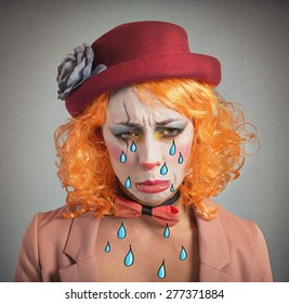 Theatrical sad and depressed girl clown crying