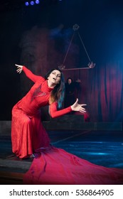 theatrical staging. Monk male and female beauty in a red dress.