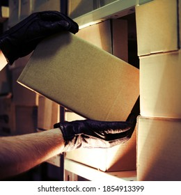 Theft of a box with a parcel in a warehouse. Man hands in gloves steal a box in a warehouse at night