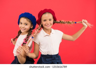 Their own style. French style girls. Cute girls having the same hairstyle. Small children with long hair plaits. Fashion girls with tied hair into braids. Little kids wearing stylish french berets.