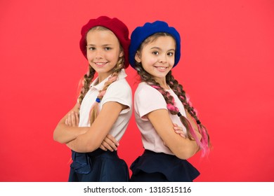 Their perfect style. Fashion girls with tied hair in braids. French style girls. Cute girls having the same hairstyle. Small children with long hair plaits. Little kids wearing stylish french berets.