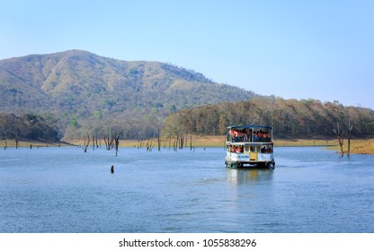 THEKKADY, IDUKKI, INDIA - MARCH 23, 2018: Boating in Periyar Lake, Thekkady. A famous tourist place in Kerala, with submerged trees in the lake surrounded by Periyar tiger reserve national park.