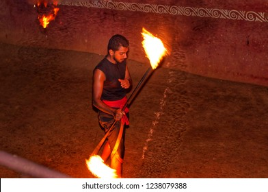 THEKKADY, INDIA -  SEPTEMBER 22, 2018: Man practicing Kalaripayattu a traditional Indian martial art and fighting system that originated in Kerala. Male holding a stick with fire on both ends.