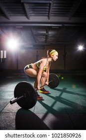 Theme of bodybuilding and training for a beautiful body, fitness. A strong girl does an exercise with a barbell, a deadlift in short shorts and a bandage on her head. In the gym with studio light