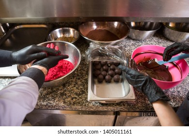 Theme cooking chocolates truffle. Close-up hand Young Caucasian woman and man cook with tattoo and in uniform prepares, makes round balltake the sweetness of cake. Confectioner covers raspberry puer.