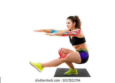 Theme kinesiology tape rehabilitation of athletes. Beautiful girl with beautiful booty doing exercise squatting onblack rug on white background. On arm and knee tape for treatment muscles and tendons.