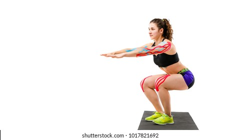 Theme kinesiology tape rehabilitation and health of athletes. Beautiful girl doing a squat exercise on a black rug on a white isolated background. On the arm and knee, a sticky colored ribbon.