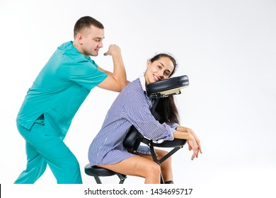 Theme massage and office. Male therapist with blue suit doing back and neck massage for young woman worker, business woman in shirt on massage chair shiatsu.