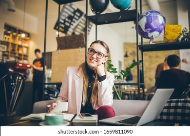 theme modern profession for young women. beautiful girl with glasses sitting at wooden table inside cafe. hand with pen makes entry in notebook diary. Man uses paper reminders and schedules.