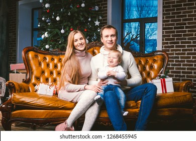 theme new year and Christmas holidays in family atmosphere. Mood celebrate Caucasian young mom dad and son 1 year old sit on a leather brown sofa at home in the living room near the Christmas tree.