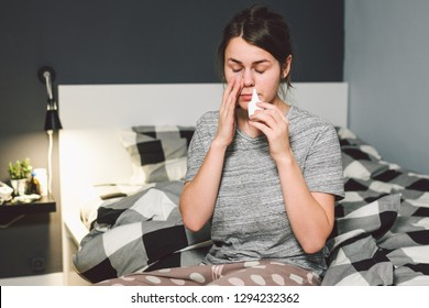 The theme is seasonal cold, runny nose flu virus infection. Young caucasian woman at home bedroom bed uses spray drops of medicine in her nose for snot. Allergic renitis and sinusitis.