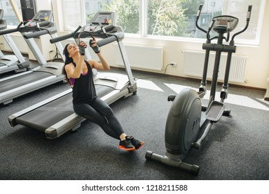 Theme is sport and sound. Girl on the treadmill and listening to music in big red headphones on her head. Traning at the gym in club. Athlete in black suit blinked her head and puts on headphones.