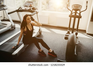 Theme is sport and sound. Girl on the treadmill and listening to music in big red headphones On her head. Woman traning at the gym in club. Concept of sport and active lifestyles.
