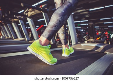 Theme of sport and weight loss. Close-up of the foot of a young strong woman in a light green sneakers on a simulator, running in the gym. Preheating before training, cardio training.
