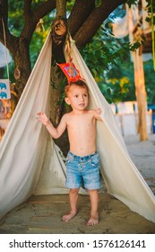 theme summer vacation, little boy, Caucasian child playing in wooded area park on playground in yard. kid Tipi wigwam tent in summer. Explore and play in nature on summer time.