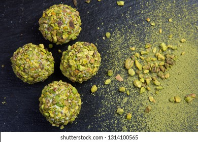 Theme sweet dessert cake handmade. Macro close-up dessert dessert sweet candy round ball white truffle ball set of white chocolate, matcha tea and pistachios on a black background.
