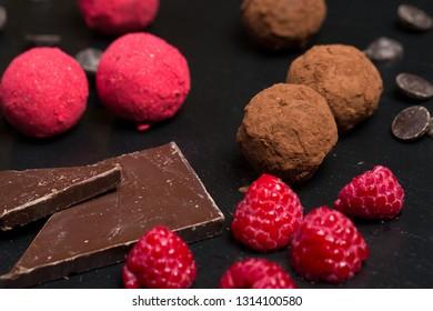 Theme sweet dessert cake handmade. Macro close-up dessert sweet candy round ball truffle set of black chocolate cocoa raspberry puer on a black background.