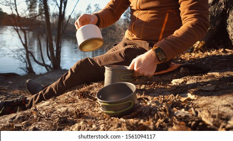 The theme of tourism is hiking and traveling in nature. Hands A Caucasian man uses equipping to cook food outside. A tourist installs a stove burner on a balloon cartridge with gas for boiling water.