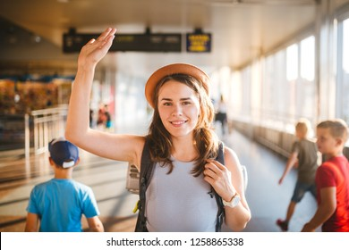 Theme tourism and travel. Young beautiful Caucasian woman in a dress and a hat with a backpack. Tourist mat in the terminal station in long corridor crossing, a schedule board, a gate to raise a hand.