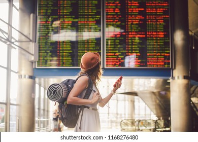 Theme travel and tranosport. Beautiful young caucasian woman in dress and backpack standing inside train station or terminal looking at a schedule holding a red phone, uses communication technology.