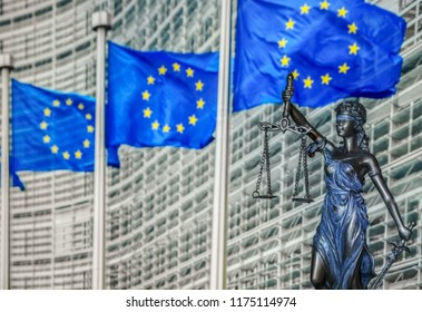 Themis and Europien Union flags on blurred buckground, shallow depth of field, focus on Themis statue. European Union law and jurisprudence