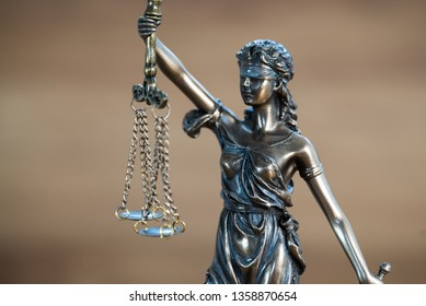 Themis, symbol of law and justice on wooden background