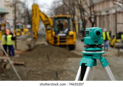 Theodolite, excavator and workers at road construction site