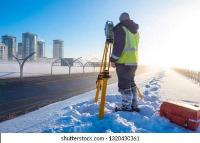 Theodolite. Topographic equipment. Theodolite stands on a tripod. Topographical measurements. Surveyor stands with a tripod. Construction works. Construction measurements.