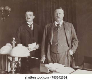 Theodore Roosevelt standing behind desk, with Asst. Presidential Secretary William Loeb, 1902. At that time, George B. Cortelyou was Secretary to the President, and succeeded by Loeb in 1904