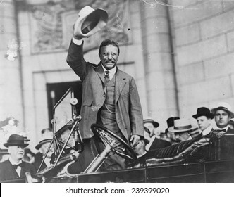 Theodore Roosevelt, waving his hat, as he stands in car. ca.1910.