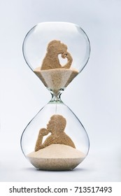 Theory of evolution concept, with falling sand taking the shape of a monkey and a man inside a hourglass