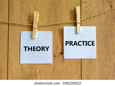 Theory and practice symbol. Wooden clothespins with white sheets of paper. Words 'theory practice'. Beautiful wooden background. Business, theory and practice concept, copy space.