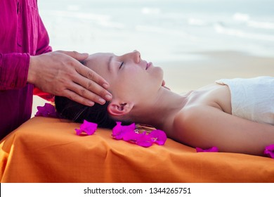 Therapeutic massage on the shore of the tropical sea. Ayurvedic relaxing massage woman in spa salon getting massage on the holiday beach.girl lying down on the table treatment procedure