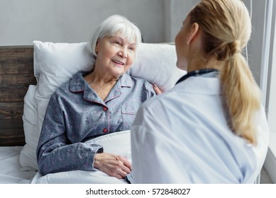 Therapeutic taking care of her client in hospital room