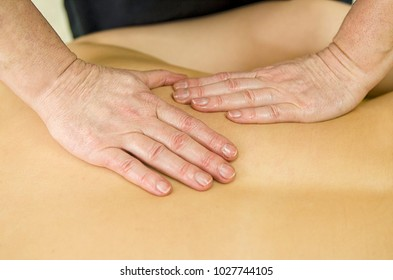 Therapeutic woman hand massage on girl back. Close up view on masseur hands on clear skin.