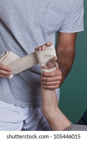 Therapist applying bandage on the hand.