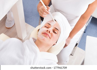 Therapist Applying A Face Mask To A Beautiful Young Woman In Spa