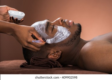 Therapist Applying Face Mask To Young African Man In Spa